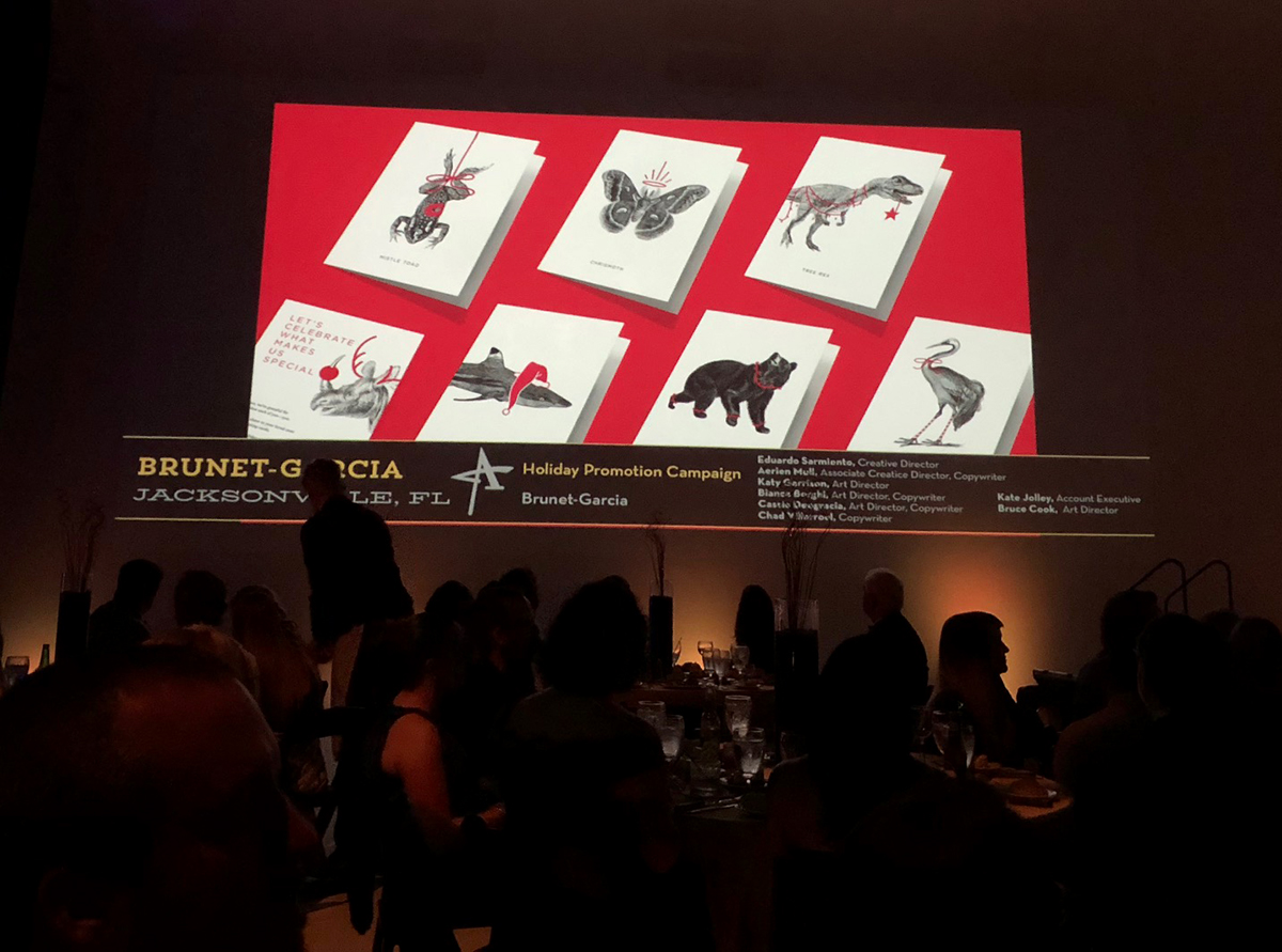 A view of the screen projecting a picture of the cards at the awards ceremony.