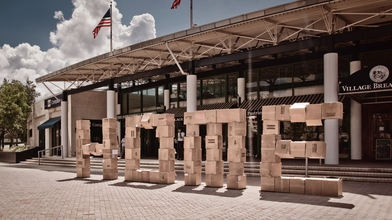 "stacked cardboard boxes that spell ""home"" in front of a shopping center"