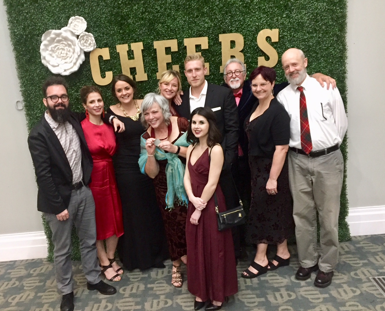 "Employees stand in front of a green background that says ""Cheers."""