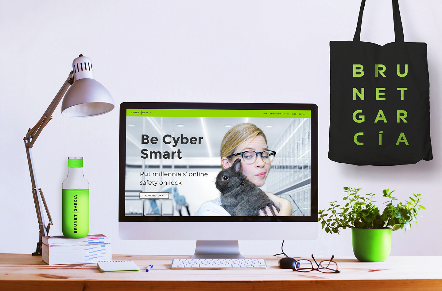 Desktop computer displays brunetgarcia.com with a green water bottle, lamp, plant, glasses, and Brunet-García bag.