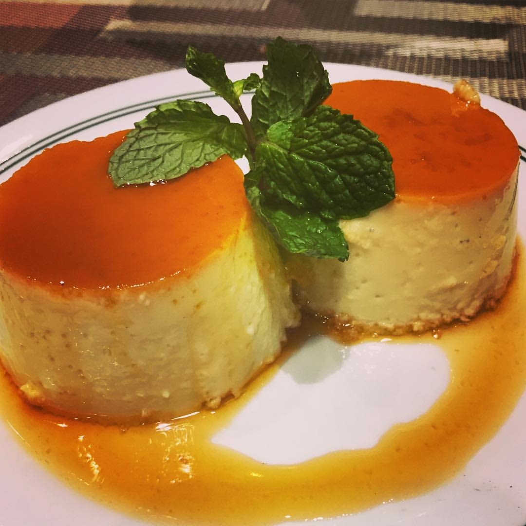 Two pieces of flan on a plate drizzled with sauce.