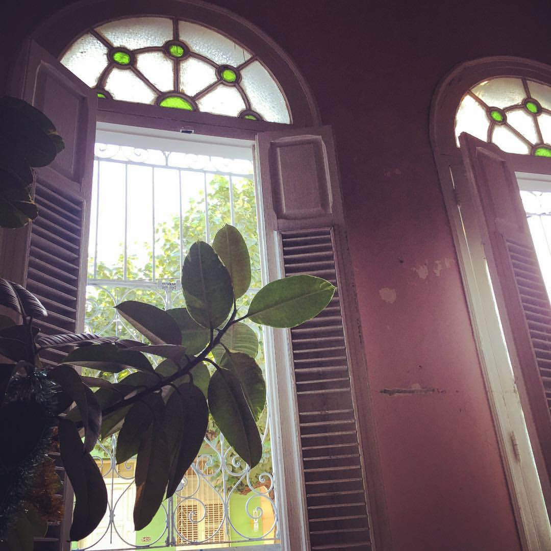 Plastic plant and chipping paint surround a window with stained glass in Calle 41, Cienfuegos.