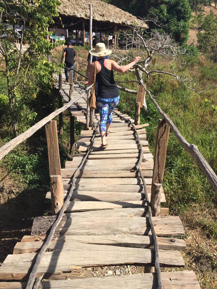 People step along a wooden bridge near a charming outpost, along the Cuba's southern coast, not far from Trinidad.