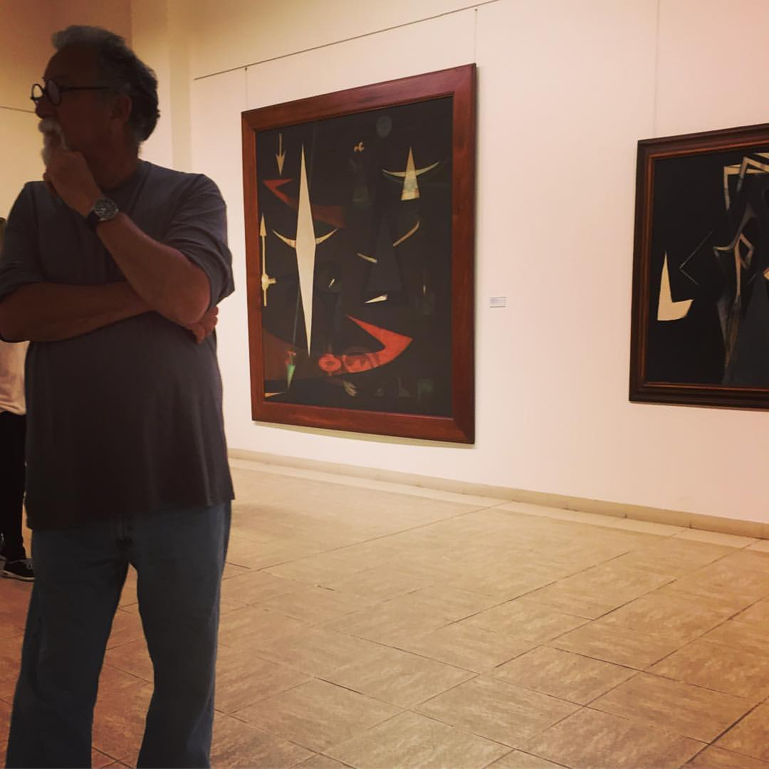Jorge Brunet-García with paintings by Wilfredo Lam.