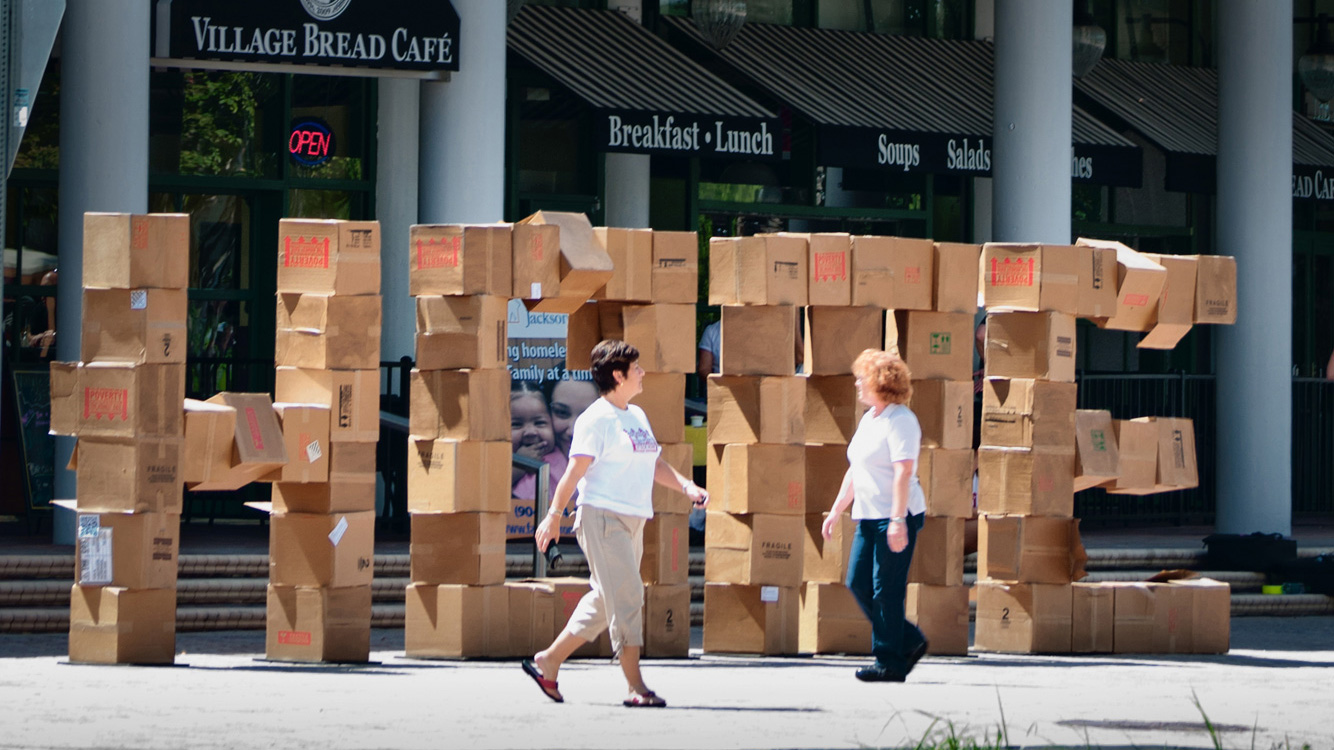"stacked boxes that read: ""home"" in front of a shopping center"