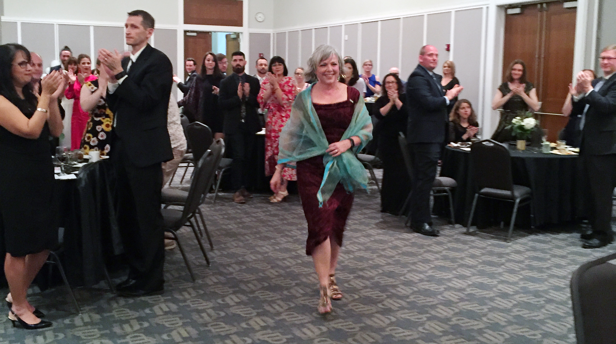 Diane Brunet-García walks to the front to a standing ovation.