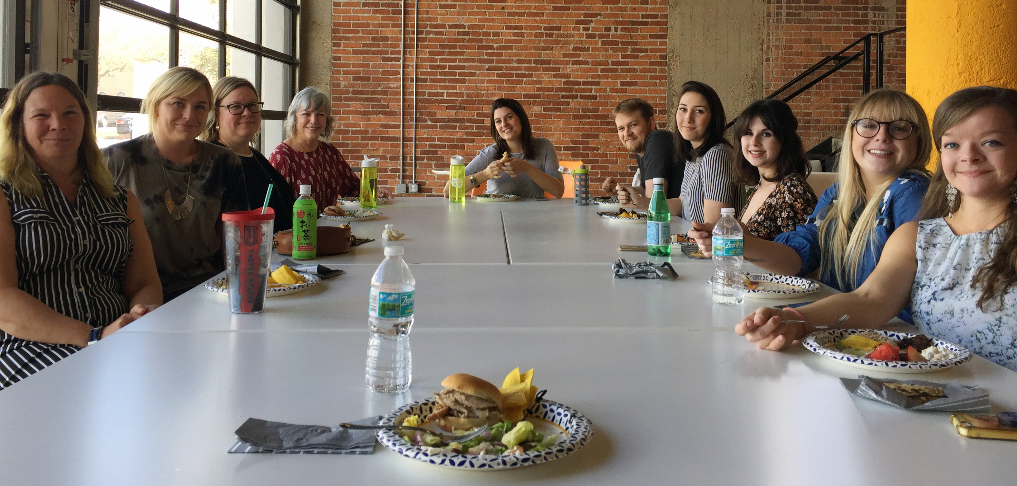 Employees gather around a table for a Lunchathon potluck.