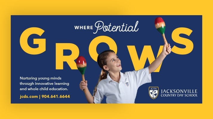 "An ad for JCDS displays a child holding maracas over the text ""Where Potential GROWS"" in the background."