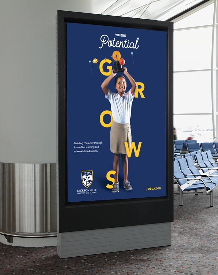 "A JCDS sign of a young girl holding a model of the solar system in front of text that says ""Where Potential GROWS"" appears in a mockup of an airport."