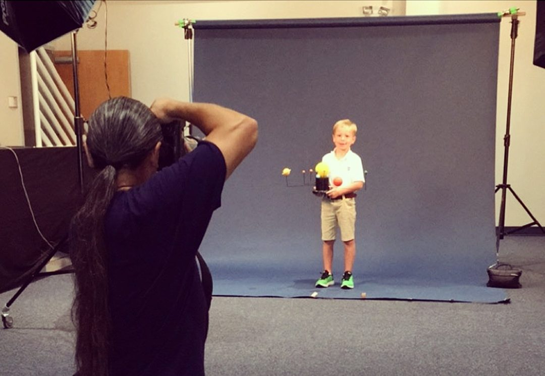 A photographer shoots a photo of a young child holding a model of the solar system while standing in front of a black background.