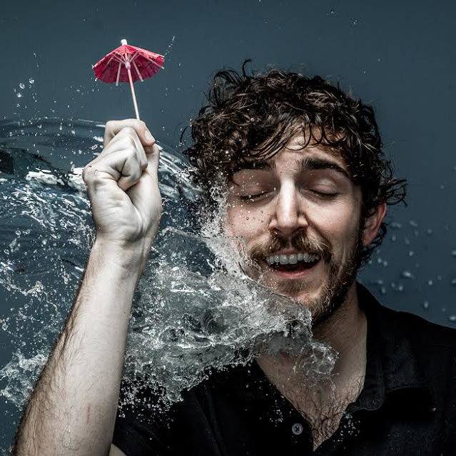 Colin Barnes holds up a tiny drink umbrella while water splashes him in the face.